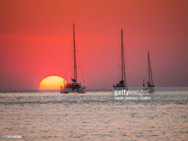 sailboat sailing on sea against orange sky - marek stefunko stock photos and pictures
