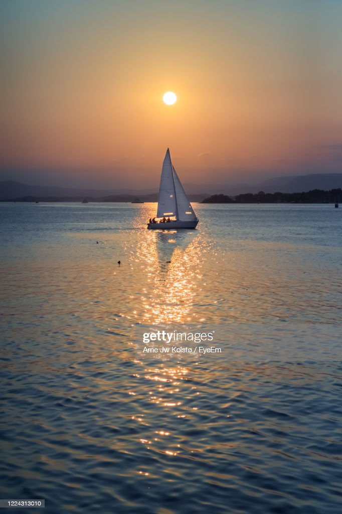 Sailboat Sailing On Sea Against Sky During Sunset : Stock Photo