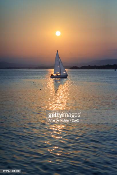 sailboat sailing on sea against sky during sunset - arne jw kolstø stock pictures, royalty-free photos & images