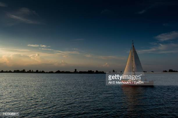 sailboat sailing on sea against sky during sunset - almere stock pictures, royalty-free photos & images