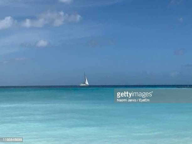 sailboat sailing on sea against sky - naomi jarvis stock pictures, royalty-free photos & images