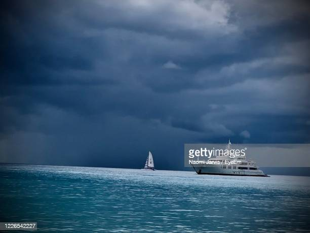 sailboat sailing on sea against storm clouds - naomi jarvis stock pictures, royalty-free photos & images