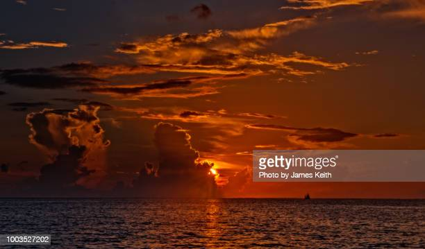 a sailboat sails into a brilliant and dramatic sunrise on biscayne bay. - miami dade county stock photos and pictures