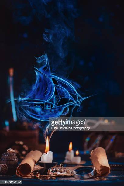 sailboat silhouette made of smoke above a burning candle in a dark pirate-themed still life - 古代の遺物 ストックフォトと画像