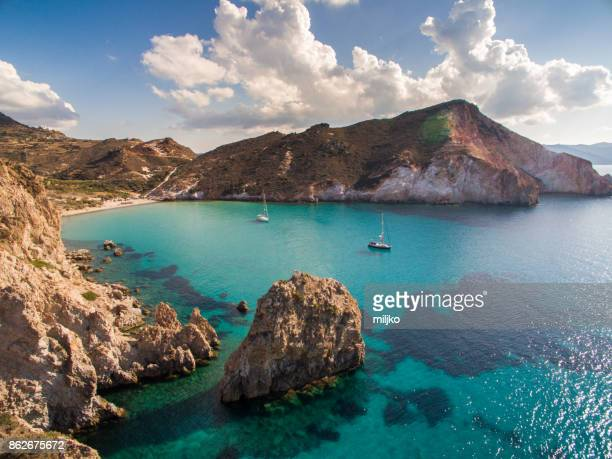 sailboats anchored in bay at milos island - greece stock pictures, royalty-free photos & images
