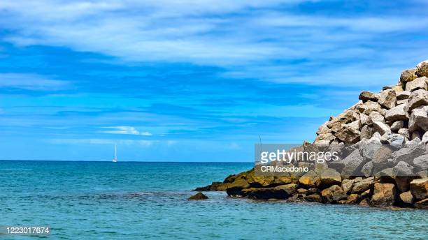 sailboats arriving at the reef of the bay of santo antonio. - crmacedonio stock pictures, royalty-free photos & images