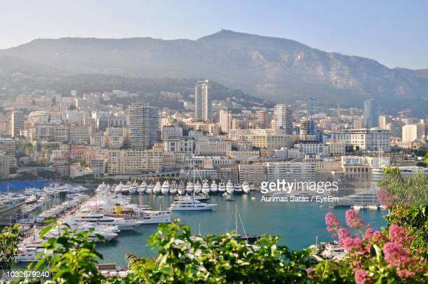 sailboats at harbor in city against mountain - monaco stock pictures, royalty-free photos & images