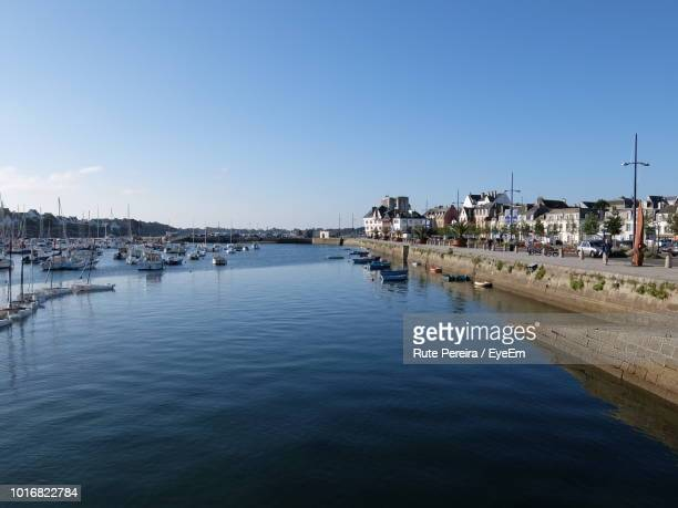 sailboats in harbor by buildings against clear blue sky - concarneau stock-fotos und bilder
