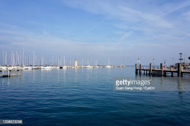sailboats in marina at harbor against blue sky - hong quan stock pictures, royalty-free photos & images