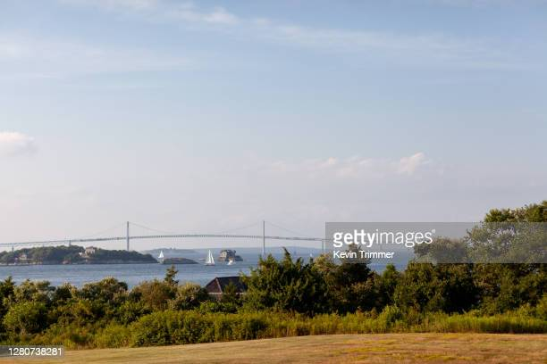 sailboats in narragansett bay with newport bridge in background - rhode island stock pictures, royalty-free photos & images