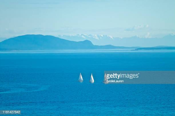 sailboats in ocean with mountains in background - lauren summers stock photos and pictures
