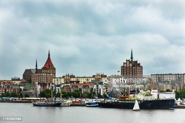 sailboats in river against buildings in city - rostock stock pictures, royalty-free photos & images