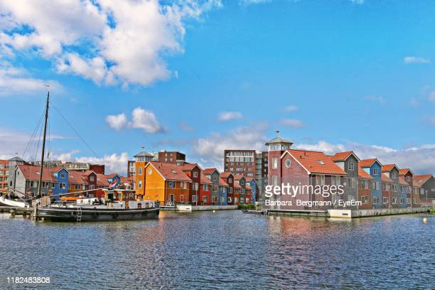 sailboats in river by buildings against sky - netherlands stock pictures, royalty-free photos & images