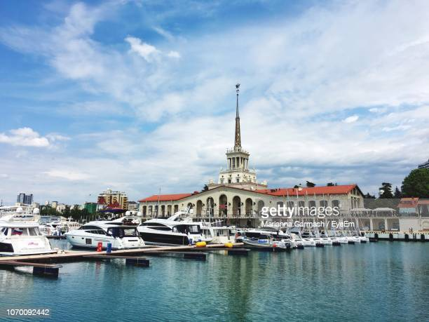 sailboats in river with buildings in background - sochi stock pictures, royalty-free photos & images