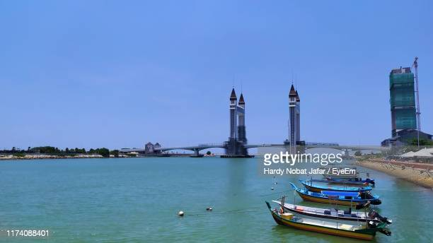sailboats in sea against sky in city - terengganu stock pictures, royalty-free photos & images