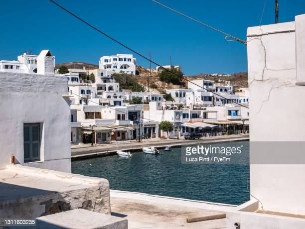 sailboats in sea by buildings against clear blue sky - greece stock pictures, royalty-free photos & images
