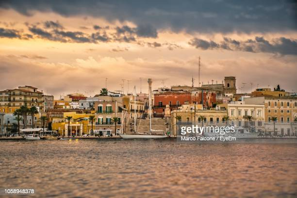 sailboats in sea by buildings against sky during sunset - ブリンディシ ストックフォトと画像