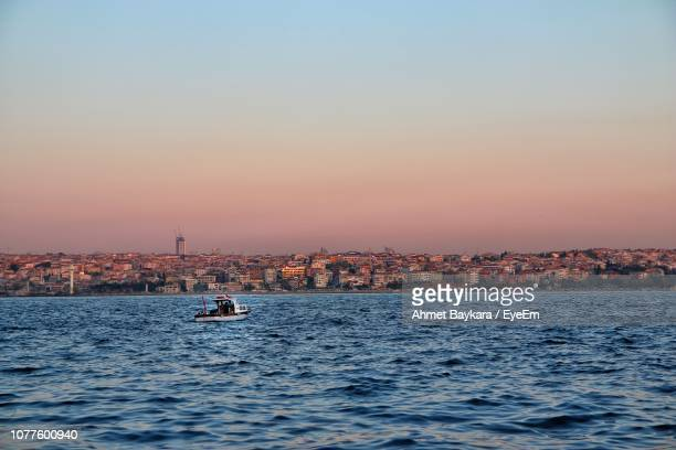Sailboats In Sea By Buildings Against Sky During Sunset