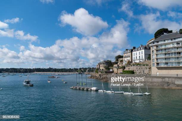 sailboats in sea by buildings against sky - dinard stock pictures, royalty-free photos & images