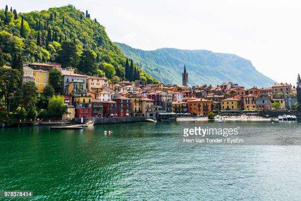 sailboats in sea by town against sky - lake como stock pictures, royalty-free photos & images