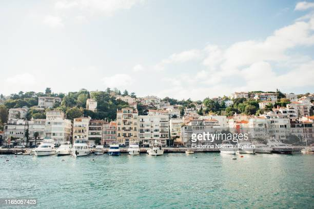 sailboats in sea by townscape against sky - nikitina stock pictures, royalty-free photos & images