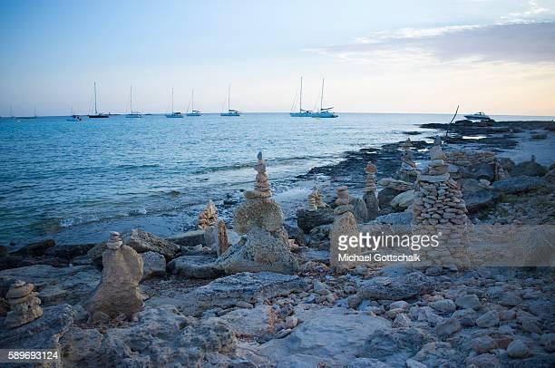Sailboats in the sea at behind Stone Sculptures at Es Trenc beach near Colonia Saint Jordi at Mallorca Island on June 30 2016 in Colonia Saint Jordi...