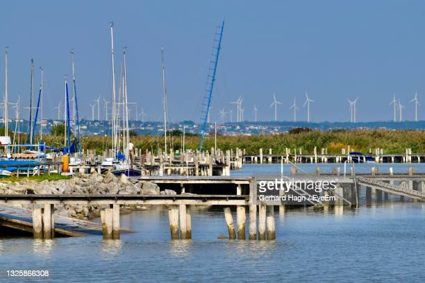 sailboats in water in marina against many wind turbines in clear sky - gerhard hagn stock-fotos und bilder