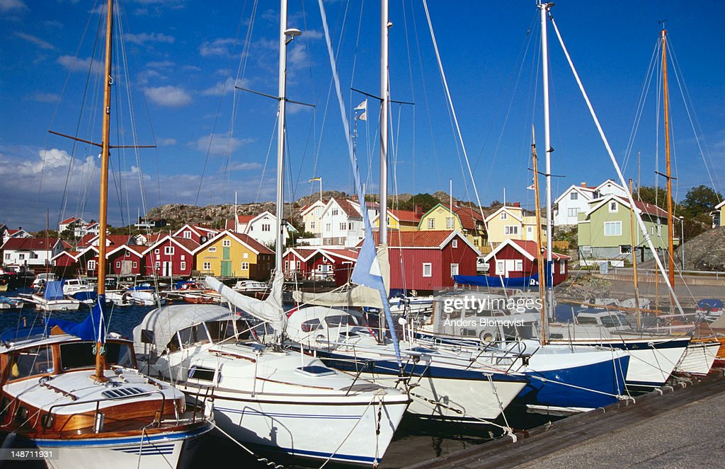 Sailboats Line Harbour Village In Background Stock Photo