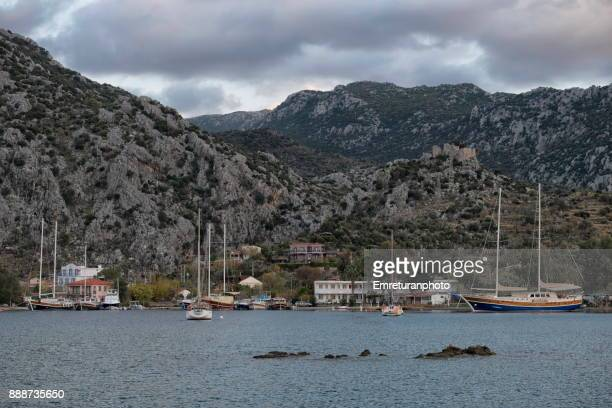 sailboats moored along the shoreline in front of selimiye village,aegean turkey. - emreturanphoto stock pictures, royalty-free photos & images