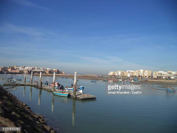 sailboats moored at harbor against blue sky - ismail khairdine stock photos and pictures