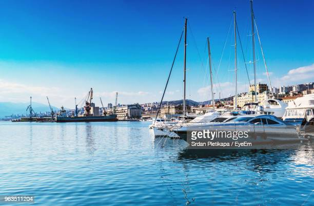 sailboats moored at harbor against blue sky - rijeka stock pictures, royalty-free photos & images