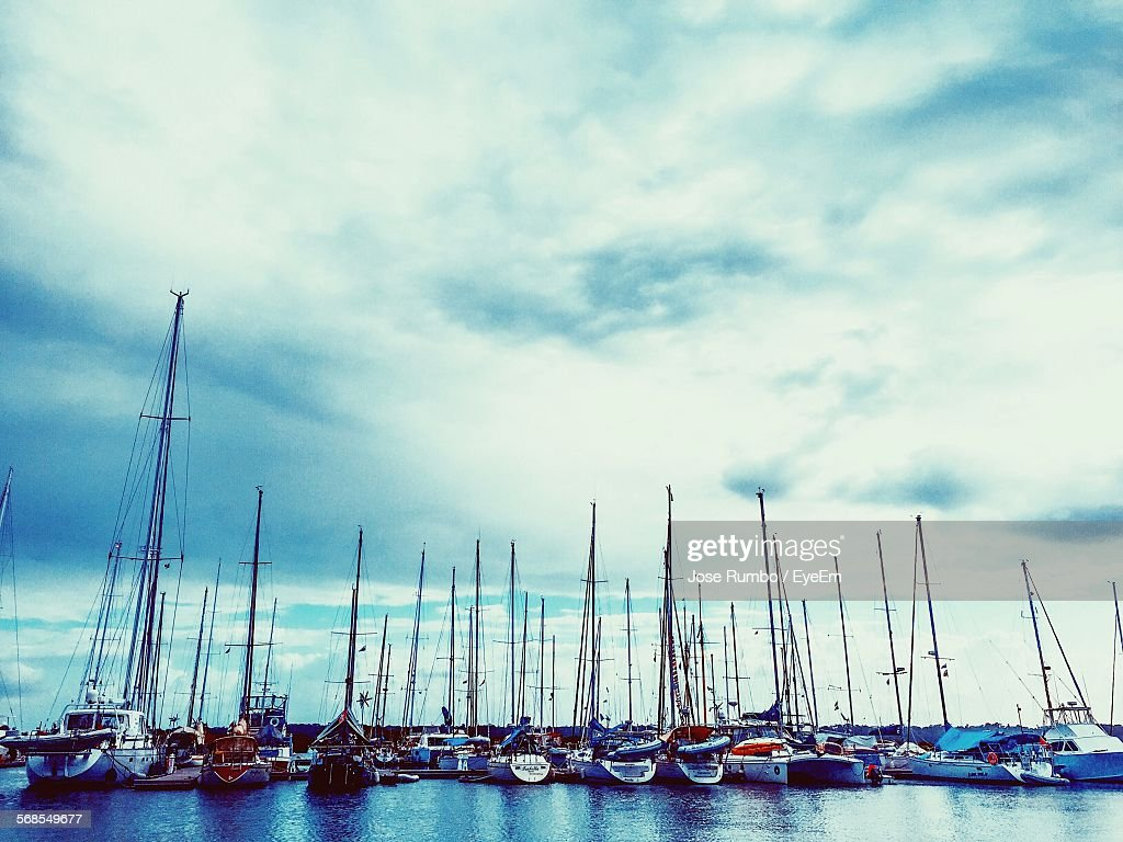 Sailboats Moored At Harbor Against Cloudy Sky : Stock Photo
