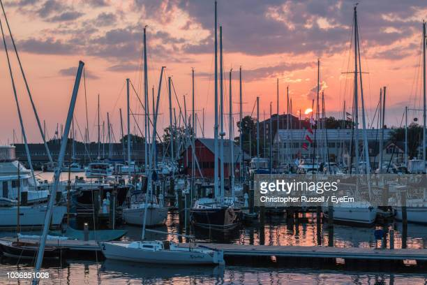 sailboats moored at harbor against sky during sunset - annapolis stock pictures, royalty-free photos & images