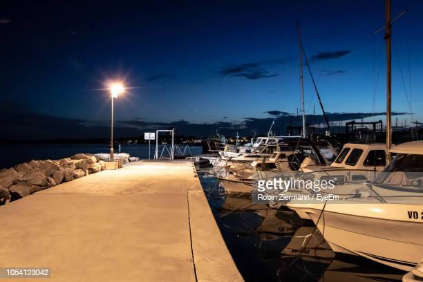 sailboats moored at harbor against sky during sunset - attraccato foto e immagini stock