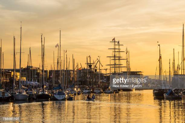 sailboats moored at harbor against sky during sunset - rostock stock pictures, royalty-free photos & images