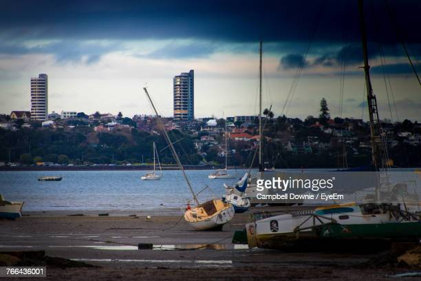 sailboats moored at harbor against sky in city - campbell downie stock pictures, royalty-free photos & images