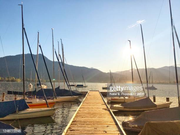 sailboats moored at harbor against sky - tegernsee stock pictures, royalty-free photos & images