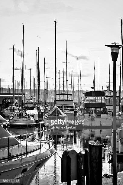sailboats moored at harbor against sky - voilier noir et blanc photos et images de collection