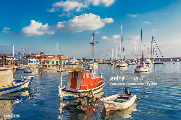 sailboats moored at harbor against sky - vgenopoulos stock pictures, royalty-free photos & images