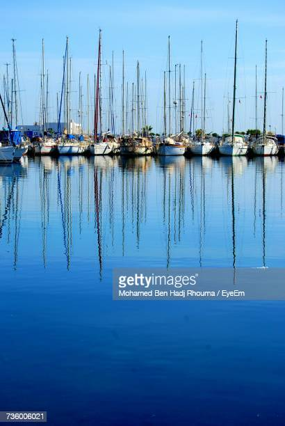 sailboats moored at harbor against sky - sousse stock pictures, royalty-free photos & images