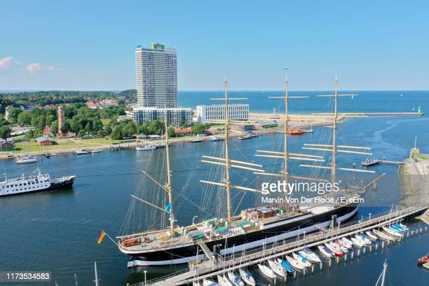 sailboats moored at harbor in city against sky - travemünde stock photos and pictures