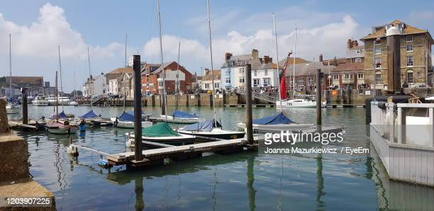 sailboats moored in canal against buildings in city - weymouth dorset stock pictures, royalty-free photos & images