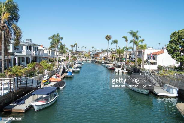 sailboats moored in canal amidst buildings in city against sky - long beach california stock photos and pictures