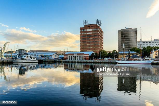 sailboats moored in harbor against buildings in city - hobart tasmania stock pictures, royalty-free photos & images