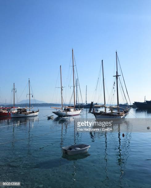 sailboats moored in harbor against clear blue sky - spetses stock pictures, royalty-free photos & images