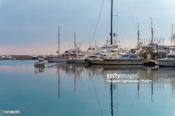 sailboats moored in harbor against sky - vgenopoulos stock pictures, royalty-free photos & images