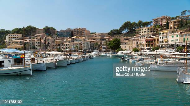 Sailboats Moored In Harbor By Buildings Against Clear Sky