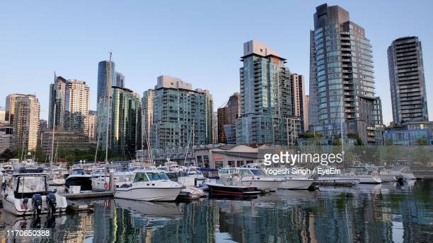 sailboats moored in harbor by buildings against sky in city - attraccato foto e immagini stock
