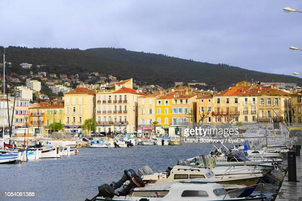 sailboats moored in harbor by town against sky - la ciotat photos et images de collection