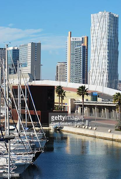 Sailboats Moored In Harbor On River By Buildings